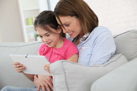 websurfing: Mother with little girl websurfing on tablet