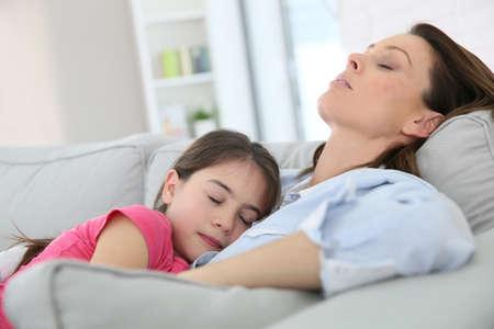 madre soltera: Madre e hija que toma una siesta en el sofá Foto de archivo