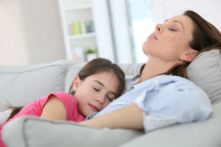 single parent: Mother and daughter taking a nap on couch