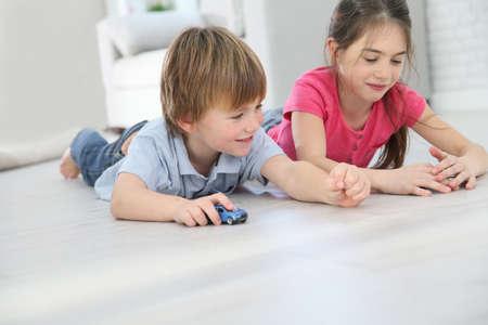 床の上に敷設、おもちゃの車で遊ぶ子供たち