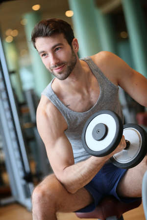 Man lifting weights in fitness center photo
