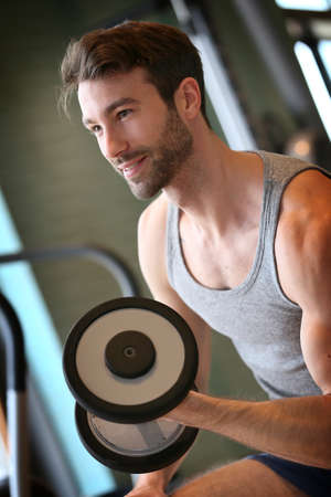 fitness center: Man lifting weights in fitness center
