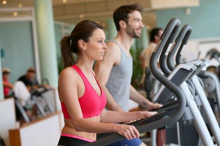 fitness men: Pareja haciendo programa de entrenamiento de cardio en el gimnasio Foto de archivo