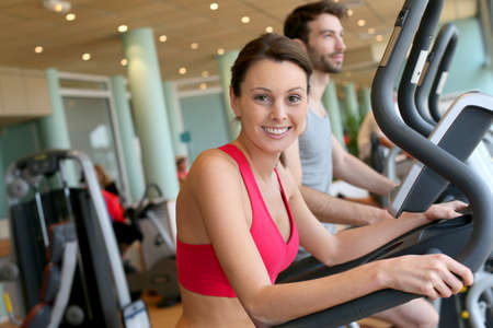 cardio fitness: Woman in fitness club using cardio equipment