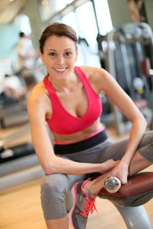 levantar pesas: Mujer atlética Alegre levantando pesas en el gimnasio