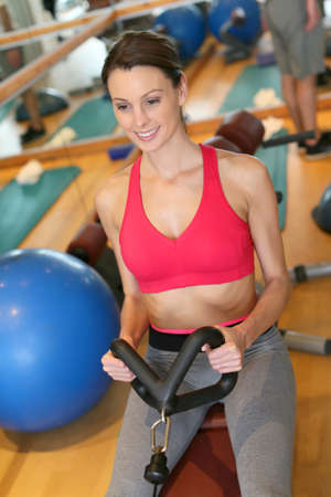 rower: Woman in fitness club exercising on rowing machine