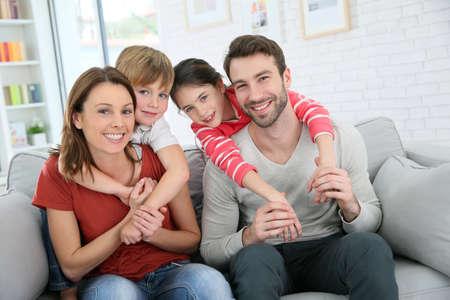 Vrolijke familie thuis zitten in de bank Stockfoto