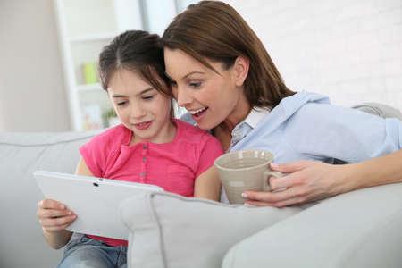 parental love: Mother with little girl websurfing on tablet