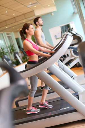 fitness club: Couple in fitness center working out on cardio machine