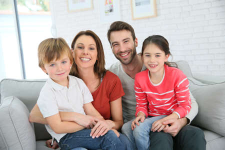 woman on couch: Cheerful family at home sitting in sofa