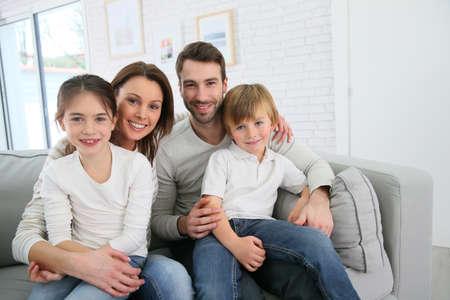 Vrolijke familie thuis zitten in bank
