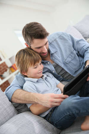 parental control: Father with little boy using digital tablet at home