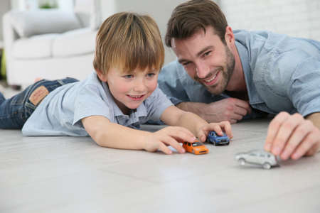 playing: Daddy with little boy playing with toy cars