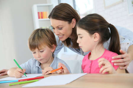 they are watching: Mother watching kids at home while they are drawing Stock Photo