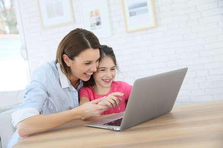 ni�os jugando videojuegos: Madre e hija que juegan en el ordenador port�til Foto de archivo