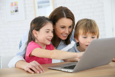 Mother with kids playing on laptop computer Stock fotó
