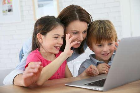 Family of three using laptop video call camera