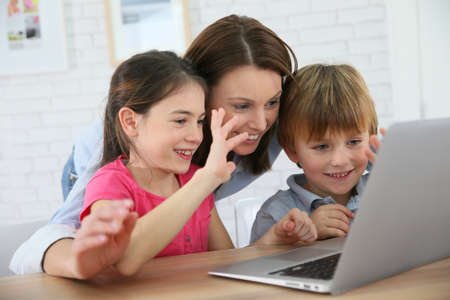 Family of three using laptop video call camera