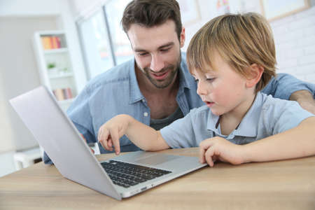 parental love: Daddy and son playing on laptop computer