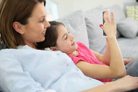 parental love: Mother and daughter playing with smartphone