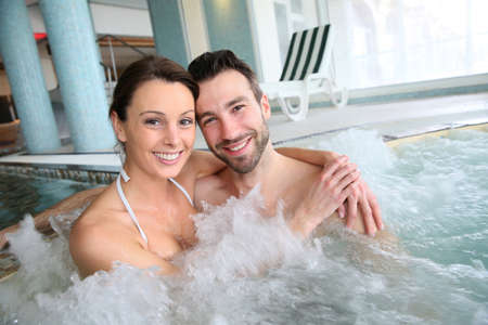 woman in bath: Couple enjoying bath in spa center jacuzzi