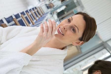 thalasso: Femme en peignoir boire du thé chaud dans une salle de relaxation