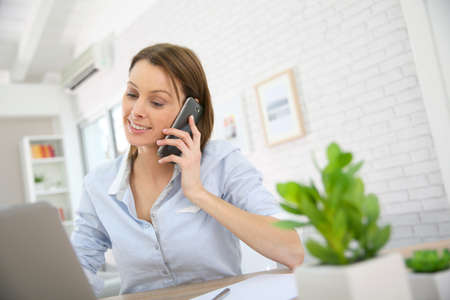 phonecall: Woman in office talking on mobile phone
