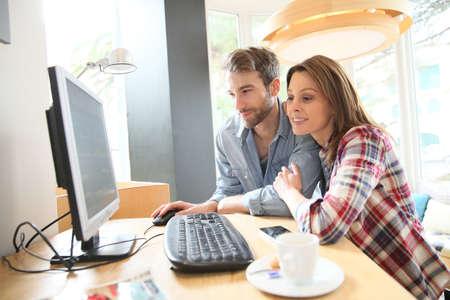 websurfing: Couple in coffee shop websurfing on desktop computer Stock Photo