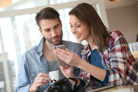 Couple in coffee shop looking at pictures on smartphone photo