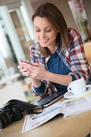 スマート フォンでテキスト メッセージを送信するブルネットの少女