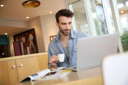 ležérní: Muž pracuje na přenosném počítači z domova Reklamní fotografie