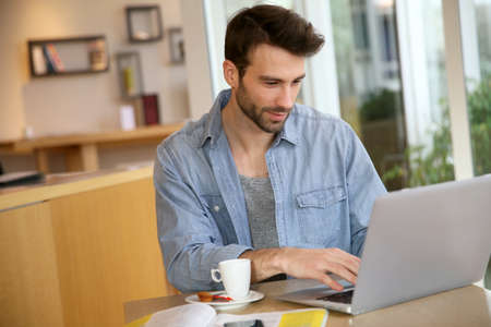 Man aan het werk op een laptop computer thuis