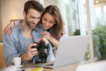 Couple watching photos on laptop computer photo