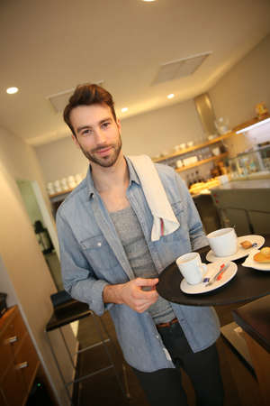 shop tender: Waiter in coffee shop holding service tray