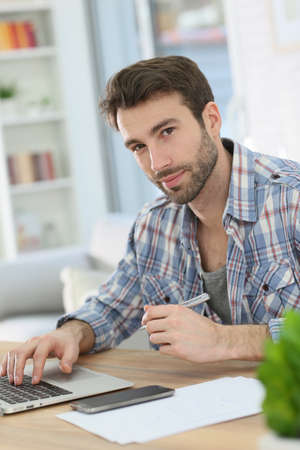 working from home: Man working from home with laptop and taking notes