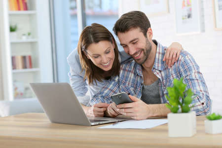 Couple at home using smartphone in front of laptop Foto de archivo