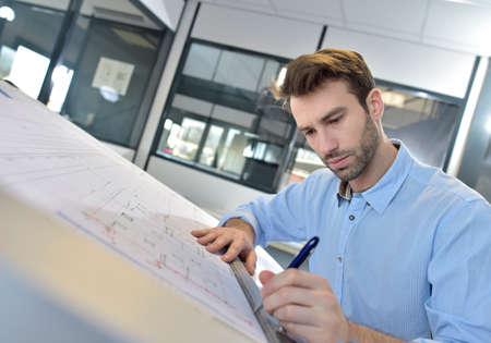 architect office: Architect designing on drafting table Stock Photo