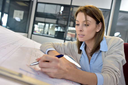 drafting table: Woman engineer working on blueprint in office Stock Photo