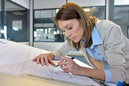 engineering drawing: Woman engineer working on blueprint in office Stock Photo