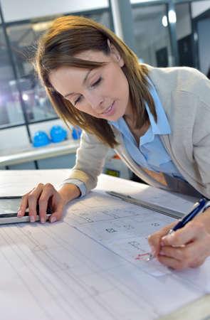 woman engineer: Woman engineer working on blueprint in office Stock Photo