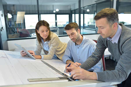 drafting table: Team of architects working on construction project Stock Photo