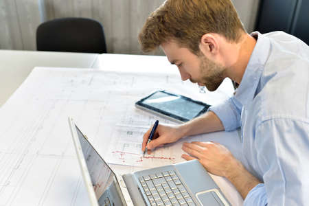 Designer in office working on project with laptop