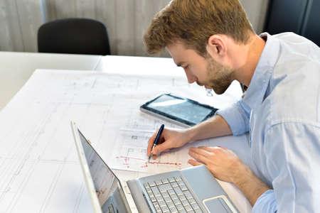 Ontwerper in kantoor werken op project met laptop Stockfoto