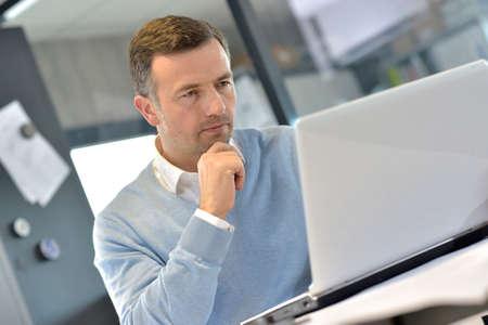 gerente: Gerente de Industrial en la oficina trabajando en la computadora portátil