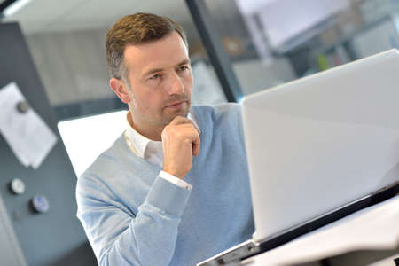 manager: Industrial manager in office working on laptop Stock Photo
