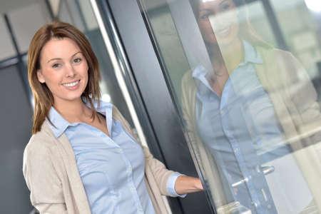 attractive office: Smiling businesswoman opening office door