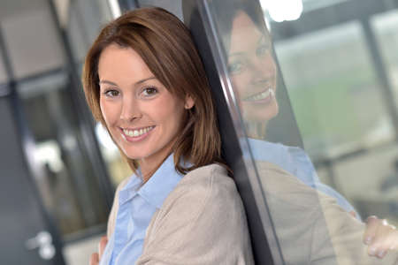 businesswoman standing: Smiling businesswoman standing in office
