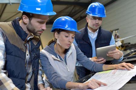 engineering: Industrial engineers meeting in mechanical factory