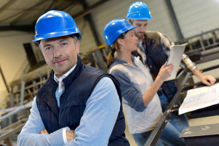 supervisor: Supervisor in factory with employees in background