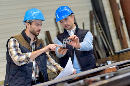 seguridad laboral: Ingeniero con el trabajador mecánico de cheques en la producción Foto de archivo